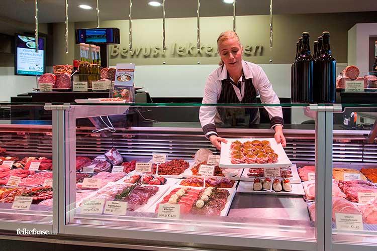 Slager legt schaal met vlees in vitrine; foto gemaakt door Feike Faase