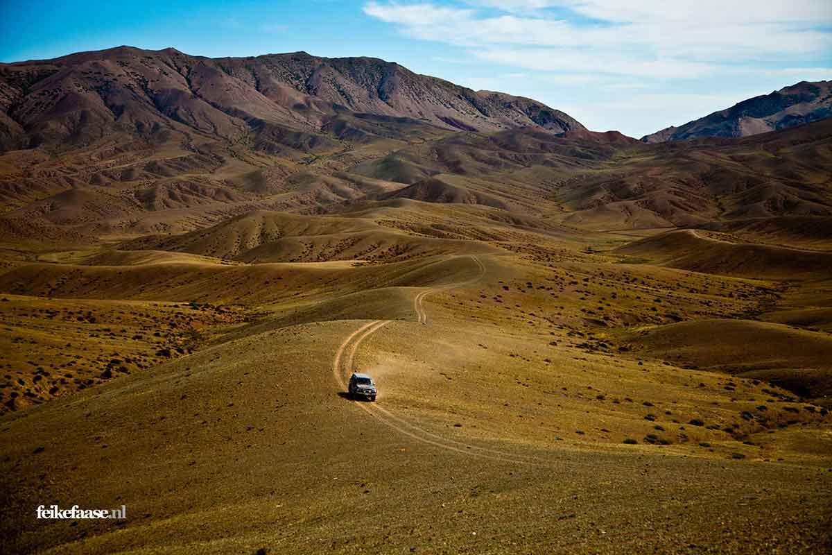 Reisfotografie: Auto rijdt door onherbergzaam landschap over spoor; foto door fotograaf Feike Faase