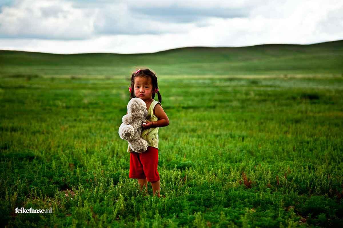 Reisfotografie: Kind in Mongolië en knuffel in groen landschap; foto door fotograaf Feike Faase