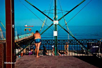 Reisfotografie: Dikke man staat aan de kust kijkend over blauwe zee; foto door fotograaf Feike Faase